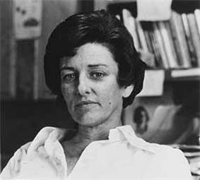 Head and shoulders monochrome portrait photo of Anne Sexton, seated with books in the background