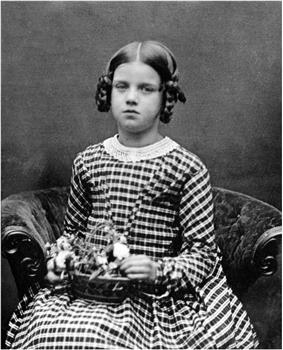 Three quarter length studio photo of seated girl about nine years old, looking slightly plump and rather solemn, in a striped dress, holding a basket of flowers on her lap.