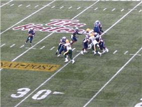 The quarterback, holding the football, looks down field for a teammate to pass to while several of his teammates push up against four opposing players attempting to reach him.