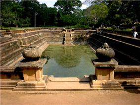 A large rectangular artificial pond with carved stone sides.