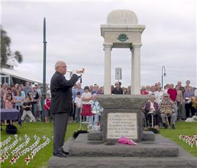 Photo of an ANZAC memorial with an elderly man playing a bugle. Rows of people are seated behind the memorial. Many small white crosses with red poppies have been stuck into the lawn in rows on either side of the memorial.