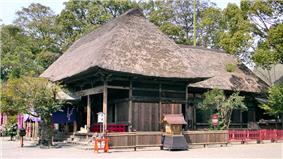 Three-quarter view of a wooden building with a thatched hip roof. Another structure of similar style extends from the back of the building.
