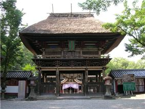 A two-storied wooden gate with a large thatched roof and a veranda with handrail on the upper floor.