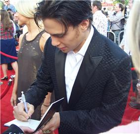 A man in a tuxedo is looking down as he signs an autograph on the red carpet.  There are people standing in the background.