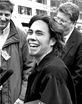 A black and white photo featuring a joyous man with a large smile who is giving an interview to a group of smiling news reporters that are crowded around him.