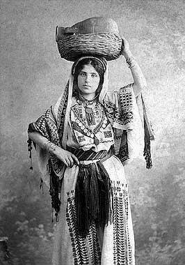 A young woman facing the camera, her left hand holding the edge of a basket with a clay pot inside that is resting on her head, her right hand at her waist. She is looking directly at the camera, wearing a long white dress of heavy material. It is embroidered with geometric designs across the chest (where there is also a v-shaped line of coins) and down the front across the length of her legs. The front part of her hair is parted in the middle, the rest covered with a long veil of the same colour and material as the dress, which is also heavily embroidered. Her arms from the elbows down are not covered by the dress or veil, but are adorned with several bracelets. Around her waist is a belt with fine fringe gathered and hanging down at the center.