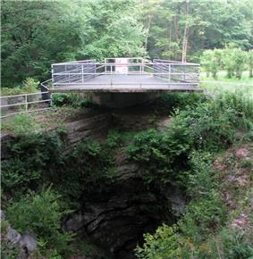 A platform with a fence around it above a deep rocky hole