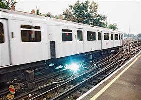 Spark coming from beneath electric passenger train
