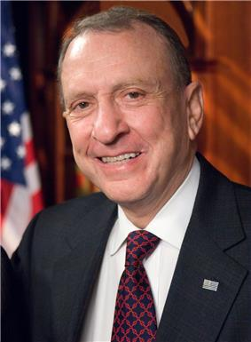 A smiling man with gray hair wearing a gray suit jacket and blue and red checkered tie stands in front of the American flag.