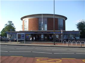 External view of a station building with a circular drum-shaped ticket hall with vertical panels of windows rising above a wider single storey entrance
