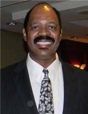 A black person, wearing a black suit and a tie, is posing for a photo.