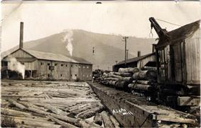 Black and white image shows a large building with a smokestack at left and many large logs in the foreground. At right is a logging train with a loader crane on a car. A bare mountain is in the background.