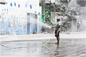 A man holding a hose and spraying volcanic ash with water