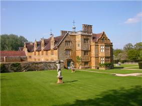 exterior of country house of Tudor period surrounded by extensive lawns