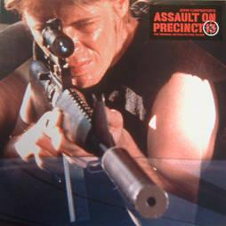 Assault on Precinct 13 soundtrack cover, featuring a still from early in the film in which one of the gang lords is sitting in the back seat of a car looking though the scope of a assault rifle.