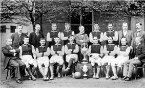 A black and white photograph showing two rows of people in front of a building; the front row are seated with two trophies in the middle, the rear row standing.