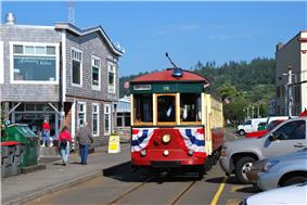 Red streetcar with creamy-white windowpanes on trolley tracks in narrow Astoria street, with green, forested hills in the background