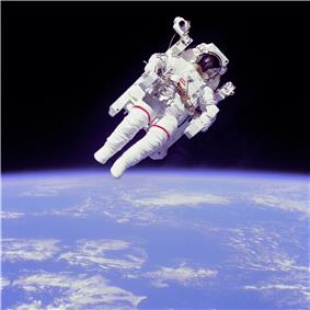 The lower half shows a blue planet with patchy white clouds. The upper half has a man in a white spacesuit and maneuvering unit against a black background.