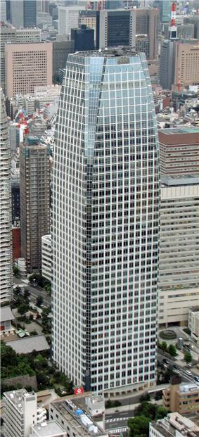 Aerial view of a glass, window-dotted high rise; the corners are cut near the top