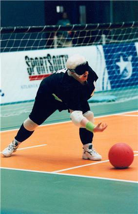 A goalballer throws the ball forward.