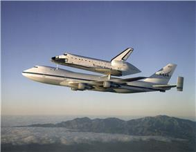 Wide-body airliner in flight with space shuttle mounted on upper fuselage.