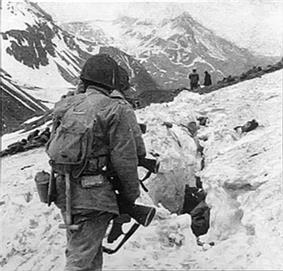A line of soldiers hiking on the side of a snow covered mountain, viewed from behind
