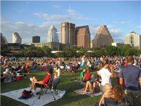Slightly elevated image taken during the evening of a crowd of people relaxing in a park, with a skyline visible in the background.