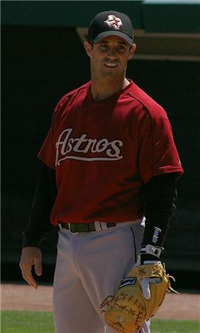 A baseball player standing at first base with his glove, wearing a red jersey with the word