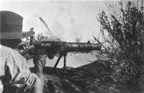 A soldier is looking through the sights of a machine gun amongst the grass in the prone position.