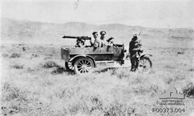 A Light Car Patrol in a landscape; driver standing beside front of car, passenger sitting in seat and machine gunner sitting in rear with gun