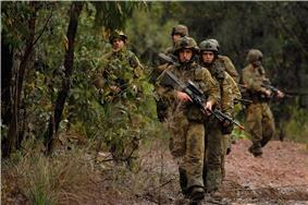 A group of Australian soldiers with rifles moving along a path in a wooded area