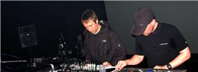 Two men performing live electronic music as a group/band in a dark room.