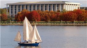 The national library is a rectangular building with tall pillars similar to a Roman/Greek style building. It stands on the shores of a landscaped lake surrounded by deciduous trees with red leaves.