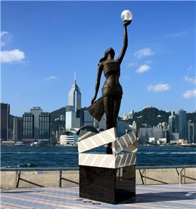A bronze statue on a pedestal, with the city skyline in the background. The pedestal is designed in the image of four clapperboards forming a box. The statue is of a woman wrapped in photographic film, looking straight up, with her left hand stretched upwards and holding a glass sphere containing a light.