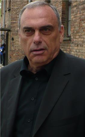 The head and upper torso of an Israeli gentleman in his 50s. He has short grey hair and is wearing a black shirt with the top button undone, and a dark grey jacket.