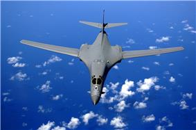 Top view of B-1B in-flight with white clouds scattered underneath. Its wings are swept fully forward as the gray aircraft flies over the ocean.