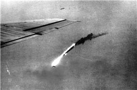 Black and white photo of flaming wreckage falling towards the ground. The wing of a plane is visible at the left-hand side of the photo.