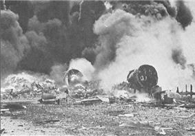 Photo of burning aircraft emitting large smoke plumes and surrounded by rubble.