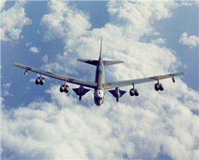 Aerial view of B-52 fly above white clouds and the sea. It carries two triangular-shaped vehicles under the wings between the fuselage and inboard engines.