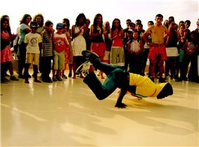 A b-boy performing in Turkey surrounded by a group of spectators.