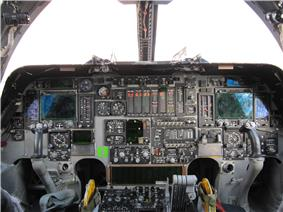 A flightdeck, dominated by a mix of new and analogue instruments. On both sides are control yokes. Light enters through the forward windows
