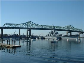 A large ship resting on the water under a bridge, smaller boats are visible in the foreground along with a ripple effect on the water.