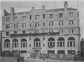 A long stone-faced façade with seven bays of windows, arched at first floor level and decreasing in size on the floors above. Prominent chimneys project above from the façade.