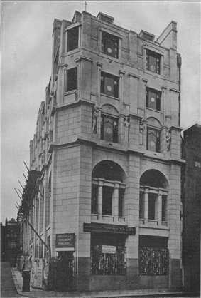 A narrow stone-faced façade with two bays of windows, arched at first floor level and decreasing in size on the floors above