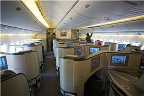 Airline business cabin. Rows of seats arranged between aisles.