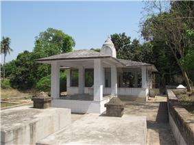 A gazebo-like stone structure pyramidal roof and a small dome