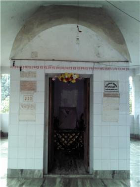 A tomb-like structure covered in while tiles with Bengali script at the entrance