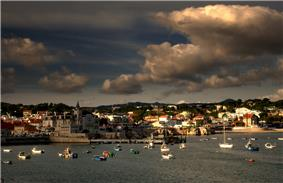 Clouds reflected off the sunset in the Bay of Cascais, with the city of Cascais
