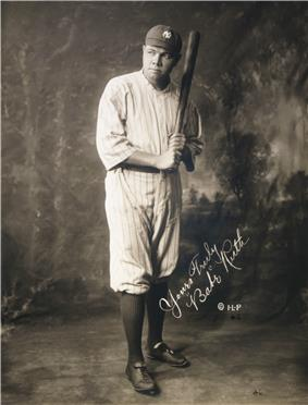 Studio photograph of a man is in uniform, posing with a bat held as if about to strike. The picture is autographed