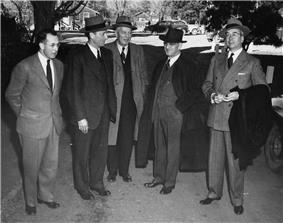 Five men in suits with hats and coats.